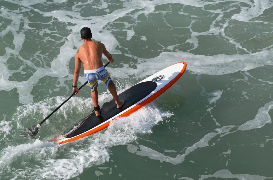 photo of man paddle boarding