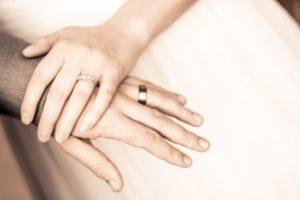 photo of hands wearing wedding bands