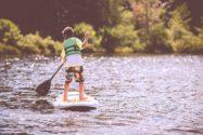 photo of boy paddleboarding