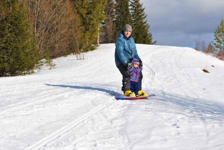 photo of child learning how to snowboard with adult
