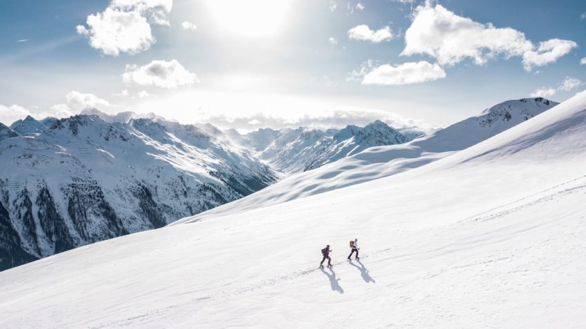 photo of two winter hikers surrounded by snowcapped mountains
