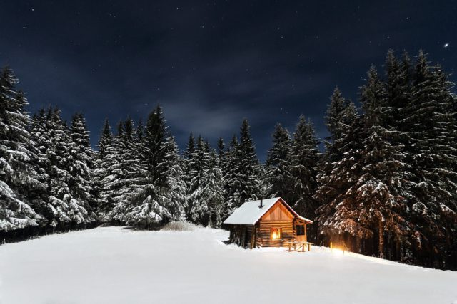hoto of a cabin at night in the snow