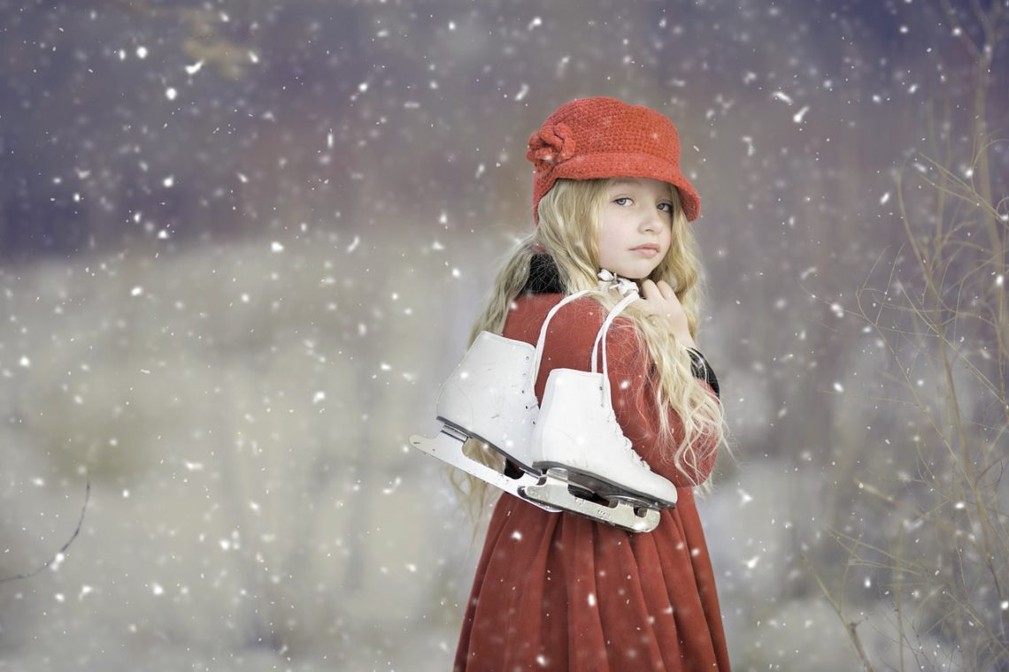 photo of a girl holding ice skates