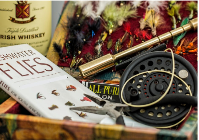 photo of a fly rod, fly fishing flies and a book about flies