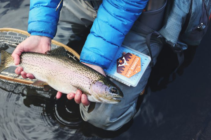man in winter jacket holding trout