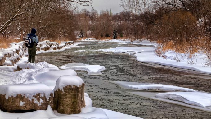 man fly fishing on a river in the winter