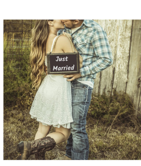 cowgirl in wedding dress and boots kissing cowboy