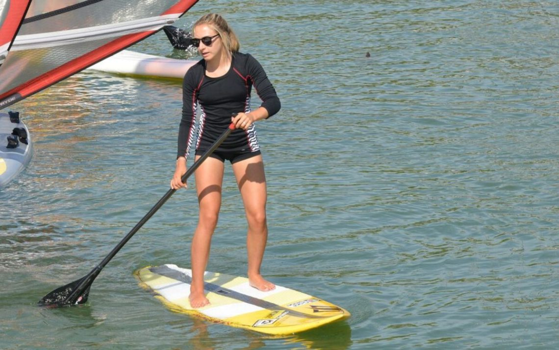 Woman wearing a rash guard while paddle boarding