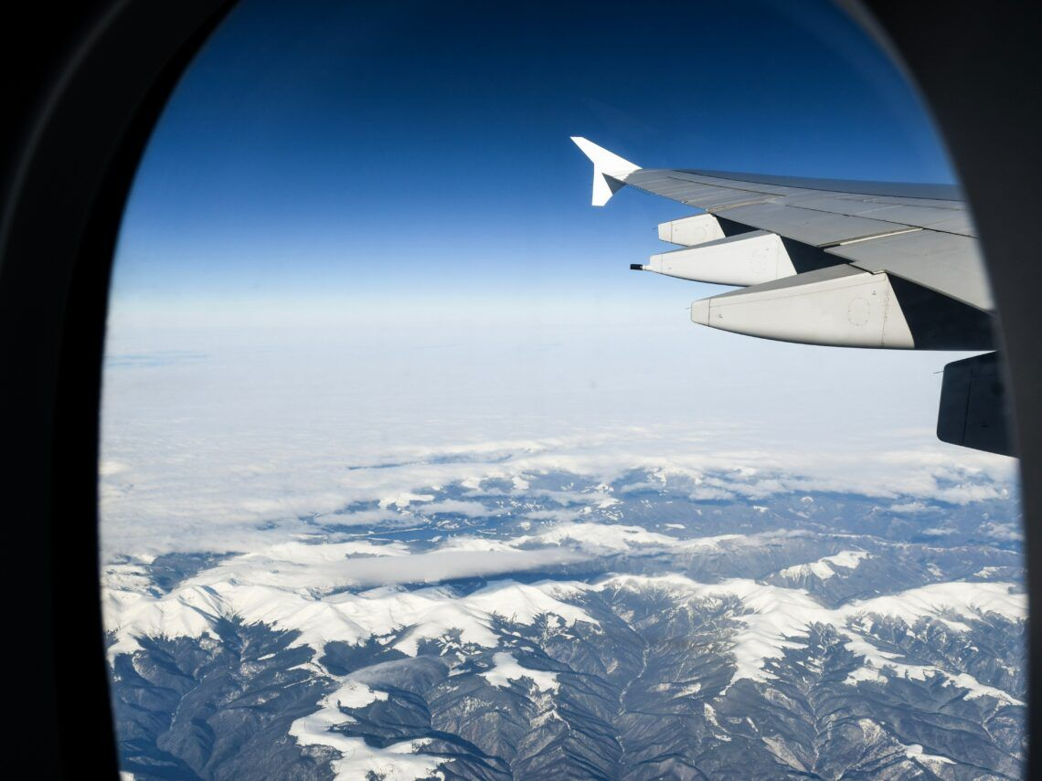 Looking out an airplane window over snowy mountains